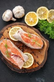 Fette di pesce fresco vista dall'alto con fette di limone sul tavolo scuro