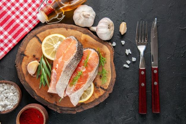 Fette di pesce fresco vista dall'alto con fette di limone aglio e condimenti sul tavolo scuro