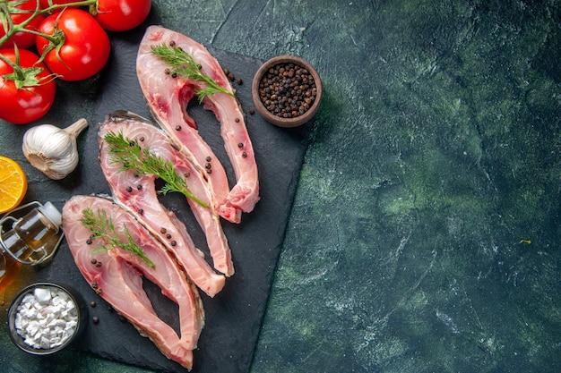 Vista dall'alto fette di pesce fresco con pepe e pomodori su sfondo blu scuro
