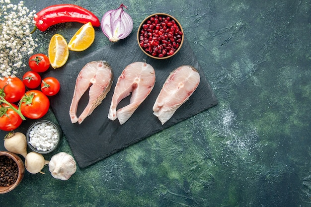 Top view fresh fish slices with red tomatoes on dark background seafood ocean meat sea meal dish food salad water pepper