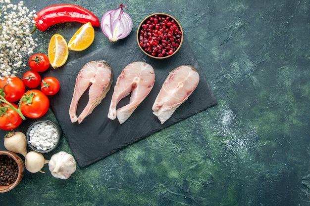 Vista dall'alto fette di pesce fresco con pomodori rossi su sfondo scuro frutti di mare oceano carne mare piatto cibo insalata acqua pepe