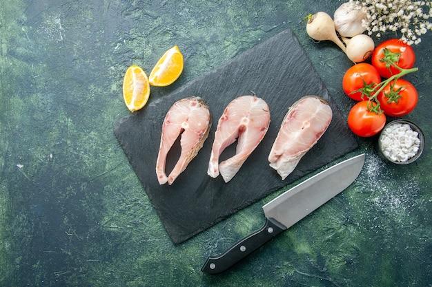 Vista dall'alto fette di pesce fresco con pomodori rossi su sfondo scuro frutti di mare oceano carne mare farina acqua pepe piatto cibo insalata Foto Gratuite