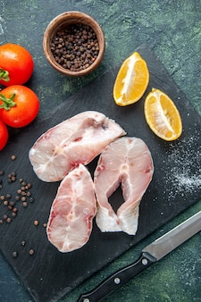 Top view fresh fish slices with red tomatoes on the dark blue surface ocean meat seafood sea meal food pepper water dish
