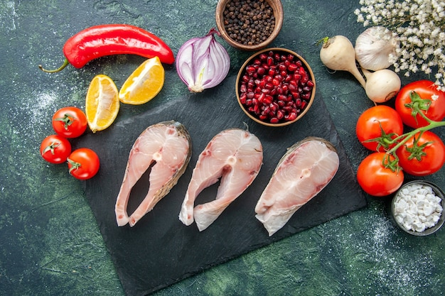 Top view fresh fish slices with red tomatoes on a dark table seafood ocean meat sea meal pepper dish food salad water