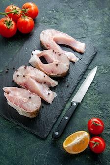 Fette di pesce fresco vista dall'alto con pomodori rossi sul piatto di pepe di cibo di acqua di farina di mare di carne dell'oceano scuro della parete