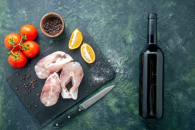 Вид сверху кусочки свежей рыбы с красными помидорами на темно-синей поверхности мясо океана морепродукты морепродукты еда перец вода блюдо вино