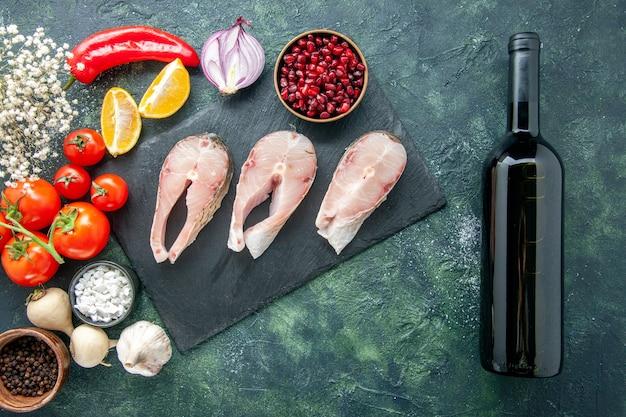 어두운 테이블에 빨간 토마토와 상위 뷰 신선한 생선 조각 해산물 바다 고기 바다 식사 요리 음식 샐러드 물 후추 와인