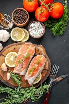 Fette di pesce fresco vista dall'alto con condimenti e fette di limone sul tavolo scuro