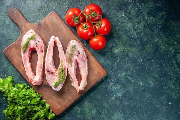 Vista dall'alto fette di pesce fresco con pomodori e verdure su sfondo scuro