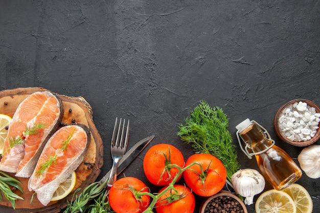 Fette di pesce fresco vista dall'alto con condimenti di pomodori e fette di limone sul tavolo scuro