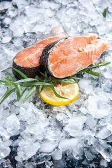 Vista dall'alto del pesce fresco diviso in due parti con fette di limone verdi su ghiaccio su sfondo nero