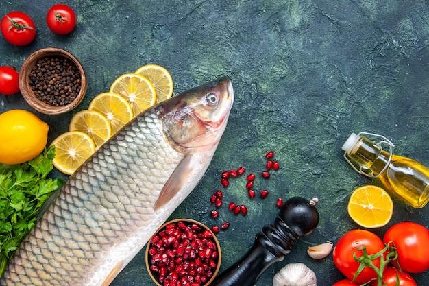 Вид сверху свежая рыба, помидоры, мельница для перца, дольки лимона, миска с семенами граната на столе