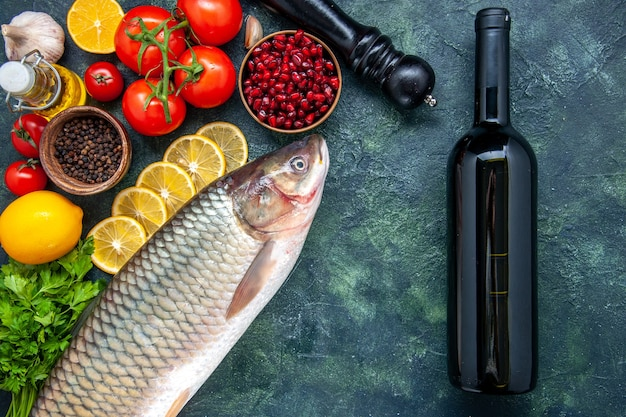 Vista dall'alto pesce fresco pomodori macinapepe fette di limone bottiglia di vino sul tavolo della cucina