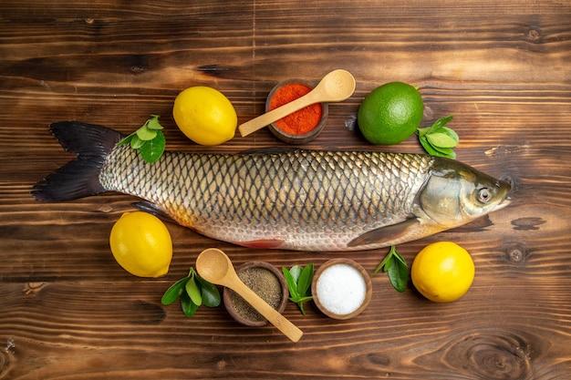 木製の机の上にレモンと調味料と新鮮な魚のトップビュー