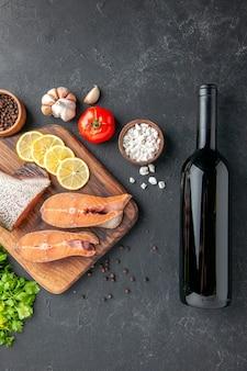 暗い背景にワインと緑のレモンボトルと新鮮な魚の上面図魚のサラダ水肉海海の食事ディナーシーフード