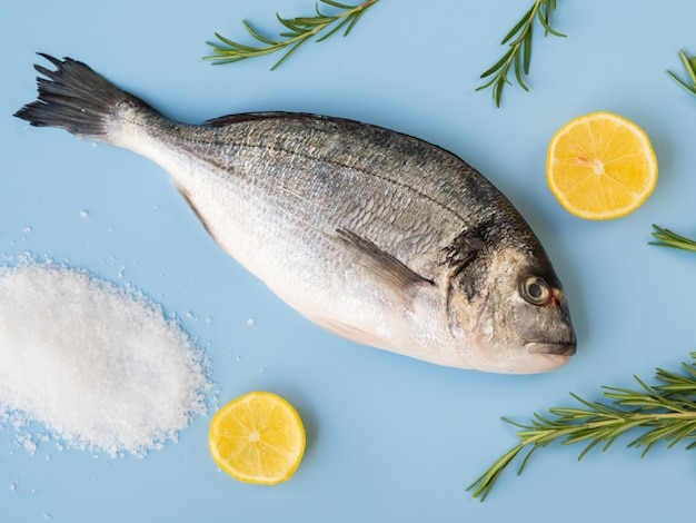 Top view fresh fish with lemon and herbs