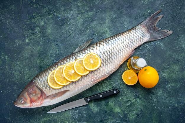 Vista dall'alto pesce fresco con fette di limone coltello limone sullo spazio libero del tavolo da cucina