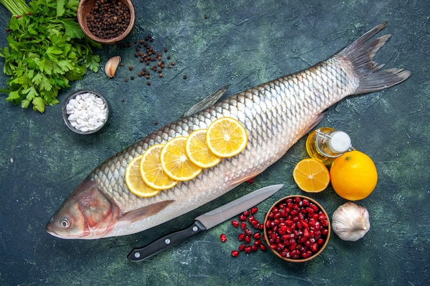 Top view fresh fish with lemon slices knife pomegranate seeds bowl lemon on kitchen table