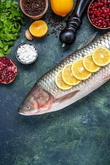 Vista dall'alto pesce fresco con fette di limone macinapepe sul tavolo della cucina
