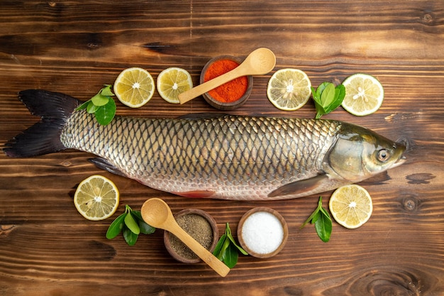 Top view fresh fish with lemon slices and seasonings on wooden desk