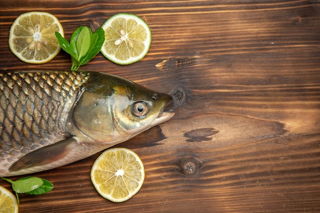 Top view fresh fish with lemon slices on a wooden desk