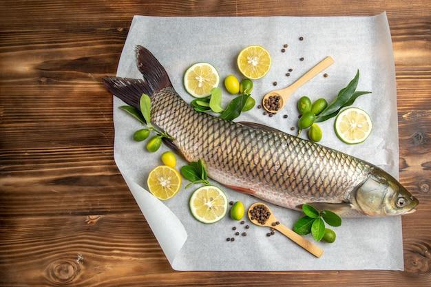 Vista dall'alto di pesce fresco con fette di limone sul tavolo in legno cibo piatto di frutti di mare oceano