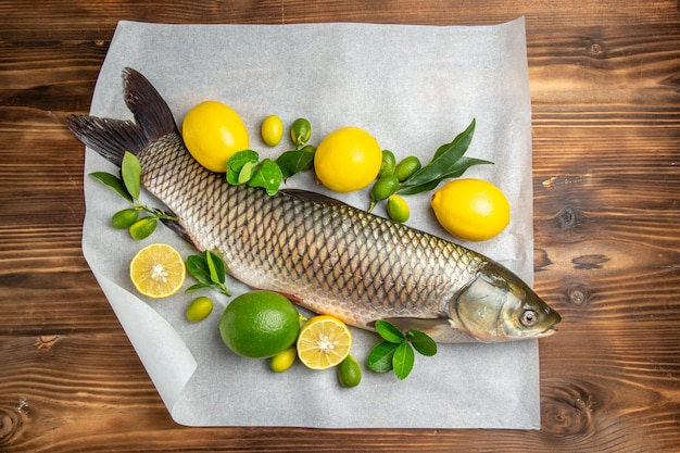 Top view fresh fish with lemons on a brown desk