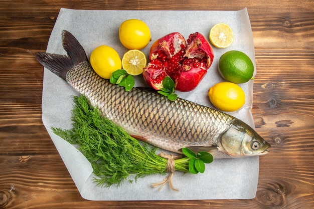 Top view fresh fish with lemons and greens on a brown desk