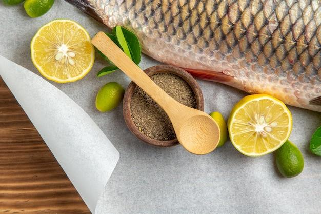 Vista dall'alto di pesce fresco con limoni e condimenti sulla scrivania marrone