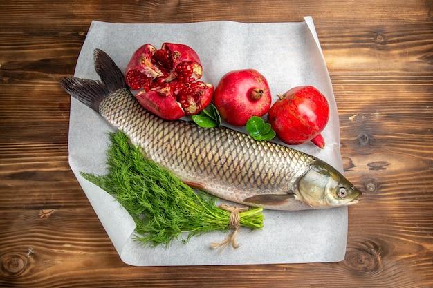 茶色の木製の机の上にザクロと新鮮な魚の上面図
