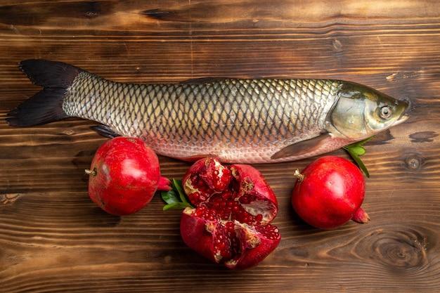 木製の机の上にザクロと新鮮な魚の平面図