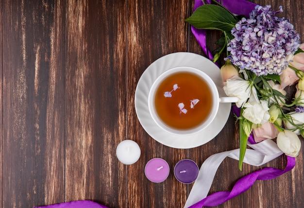 Vista dall'alto di fiori freschi come le rose tulipano gardenzia con una tazza di tè su uno sfondo di legno con spazio di copia