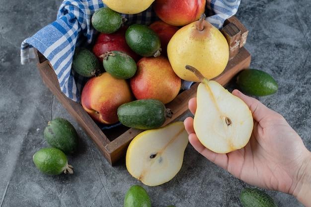 Vista dall'alto del cesto di frutta fresca. femmina che tiene mezza pera tagliata.