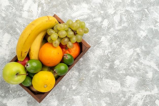 Vista dall'alto composizione di frutta fresca banane uva e feijoa su sfondo bianco frutta dolce vitamina salute fresca