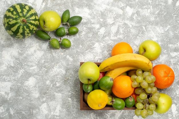 Vista dall'alto composizione di frutta fresca banane uva e feijoa su sfondo bianco frutta matura mellow vitamina salute fresca