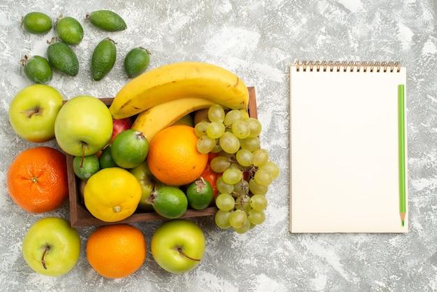 Vista dall'alto composizione di frutta fresca banane uva e feijoa su sfondo bianco frutti mellow vitamina salute fresca matura