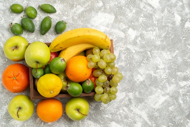 Vista dall'alto composizione di frutta fresca banane uva e feijoa sullo scrittorio bianco frutta dolce vitamina salute fresca