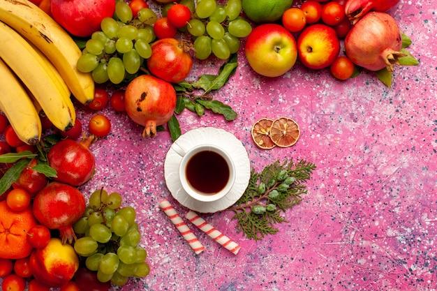 上面図新鮮な果物の組成ピンクの表面にお茶とカラフルな果物