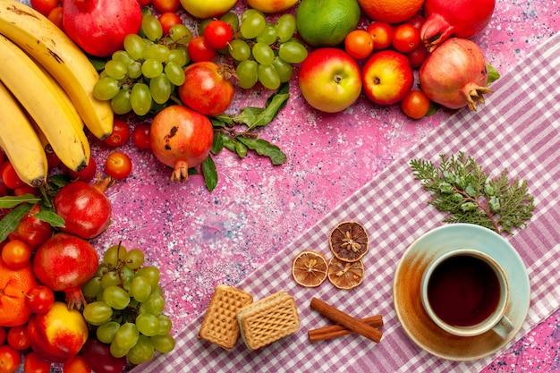 Vista dall'alto composizione di frutta fresca frutti colorati con una tazza di tè e cialda sulla superficie rosa