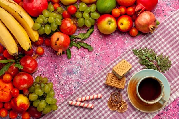 Vista dall'alto composizione di frutta fresca frutti colorati con una tazza di tè e cialde sulla superficie rosa
