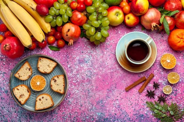 Вид сверху композиция из свежих фруктов, красочные фрукты с вкусными нарезанными тортами и чаем на розовом столе