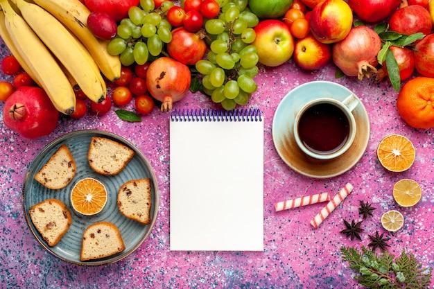 Vista dall'alto composizione di frutta fresca frutta colorata con deliziose torte a fette e tè sulla scrivania rosa