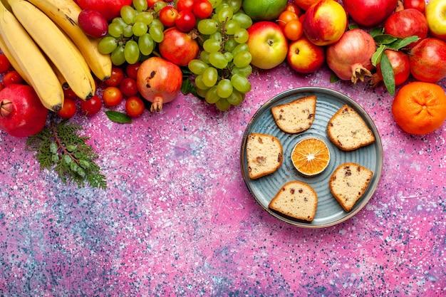 Композиция из свежих фруктов, вид сверху, красочные фрукты с нарезанными тортами, розовый стол