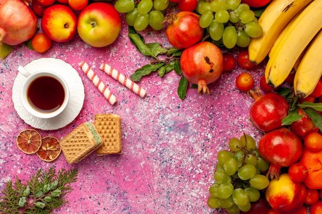 Vista dall'alto composizione di frutta fresca frutti colorati con tè e cialde sulla superficie rosa