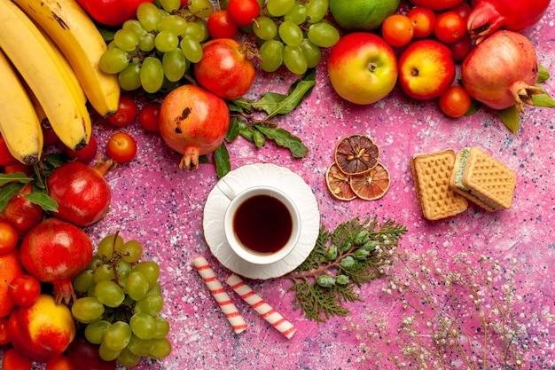 Vista dall'alto composizione di frutta fresca frutti colorati con cialde e tazza di tè sulla superficie rosa