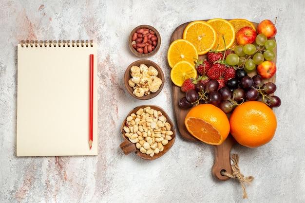 Vista dall'alto della composizione di frutta fresca arance fresche uva noci e fragole su superficie bianca