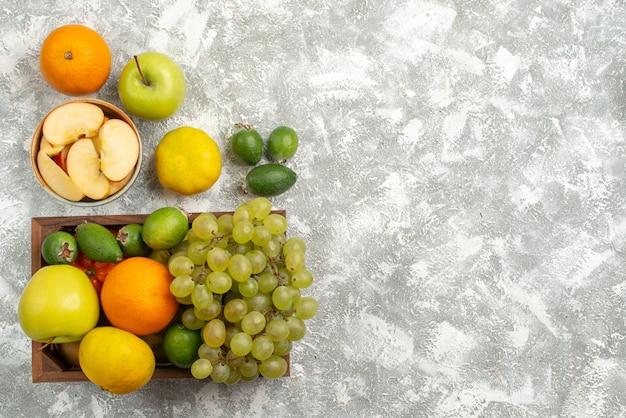 Вид сверху композиция из свежих фруктов виноград фейхоа и яблоки на белом фоне фрукты экзотические цитрусовые свежие
