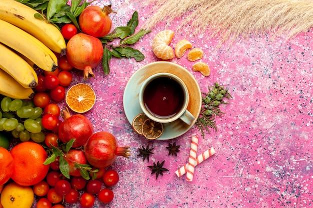 Vista dall'alto composizione di frutta fresca con una tazza di tè sulla superficie rosa chiaro