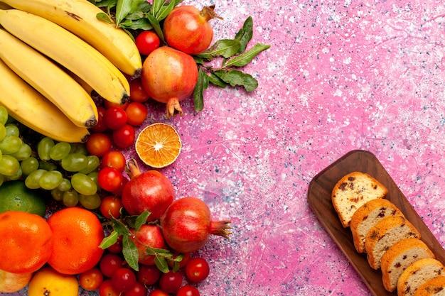 Композиция из свежих фруктов с нарезанными тортами на светло-розовом столе