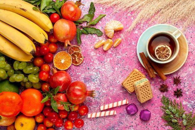 淡いピンクの机の上にワッフルとお茶とトップビューの新鮮な果物の組成物
